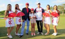 Oscar Borda, su hija (sosteniendo el trofeo) y Mathew Goggin con azafatas de Claro