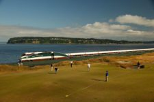 The 16th hole is set up for Wednesday's practice round as a train speeds by along Puget Sound (cortesía USGA)